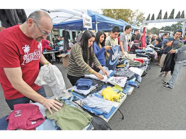 South Valley Church Elder Scott Jensen, left, and church volunteers sort through the hundreds of pounds of donated clothing by size and gender as attendees, right, check out clothing during the street feast in Newhall on Thanksgiving. Photo by Dan Watson/The Signal.