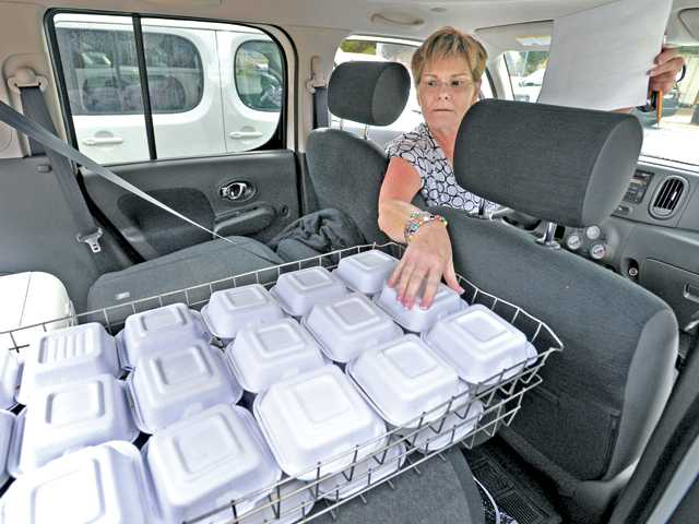 Santa Clarita Valley Senior Center home delivery volunteer Colleen Benn checks her list against the meals in the back of a van as she prepares to deliver Thanksgiving dinners to home-bound seniors on Thursday. Photo by Dan Watson/The Signal.