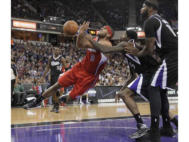 Los Angeles Clippers forward Jared Dudley, left, is fouled by Sacramento Kings forward John Salmons, center on Friday night in Sacramento.