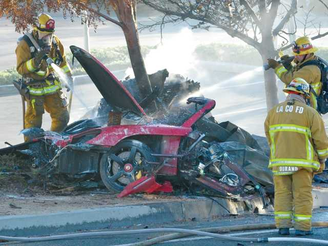 Firefighters spray water on the wreckage of a Porsche sports car that crashed into a light standard on Hercules Street in the Rye Canyon Industrial Park in Valencia on Saturday. Signal photo by Dan Watson