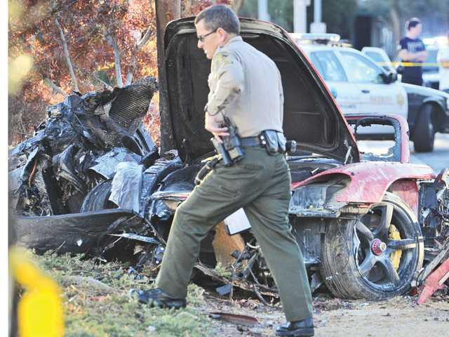 A sheriff's deputy at the scene of a crash in the Rye Canyon Business Park in Valencia where two people were killed when a Porsche crashed Saturday. Signal photo by Dan Watson