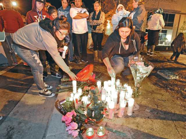 Nancy Chavez, left, and Maria Ramirez place candles at the scene on Sunday in Valencia where actor Paul Walker and another person died on Saturday in a car accident.