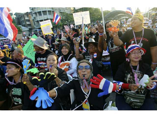 Anti-government protesters wave Thai national flags and clapping tools during rally at the Democracy Monument in Bangkok, Thailand on Sunday.