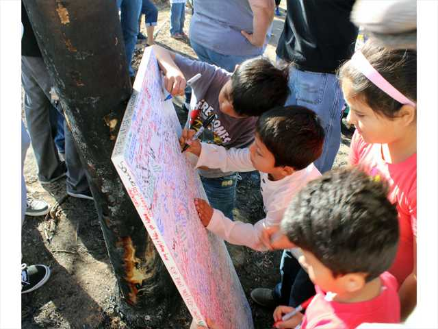 Children write messages on a canvas set against a burned tree trunk at the roadside memorial for actor Paul Walker in Valencia on Sunday.  Walker is believed to have been a passenger in the car that crashed and burned on Saturday, Nov. 30 as a charity event at a nearby car shop was winding down. Photo by Ryan Fonseca/The Signal.