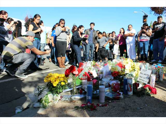 Hundreds gather around a roadside memorial for actor Paul Walker on Hercules Street in Valencia on Sunday, the day after he and Valencia business owner Roger Rodas were reportedly killed in a fiery crash. Photo by Ryan Fonseca/The Signal.