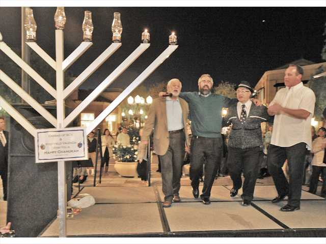 From left, Rabi Ron Hauss, Rabi Choni Marozov, Cantor Kenny Ellis and Rabi Mark Blazer dance on stage after lighting the menorah before the dozens of attendees at the annual Festival of Lights menorah-lighting ceremony held at the Westfield Valencia Town Center Mall on Sunday. Photo by Dan Watson.