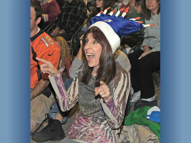 Wendy Hersh, wearing a menorah hat, leads a group of youngsters as she sings Hanukkah songs for the dozens of attendees at the annual Festival of Lights. Photo by Dan Watson.