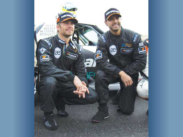 This photo from the Facebook page of the custom car shop Always Evolving shows Paul Walker, left, and Roger Rodas at a 2010 racing event.