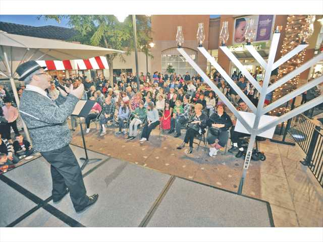 Cantor Kenny Ellis sings the Hanukkah song 'Swingin' Dreidel' on stage for the dozens of attendees at the annual Festival of Lights menorah-lighting ceremony held at the Westfield Valencia Town Center Mall on Sunday. Photo by Dan Watson.