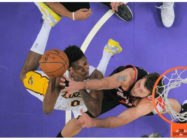 Los Angeles Lakers forward Nick Young, left, puts up a shot against Portland defenders on Sunday at the Staples Center.