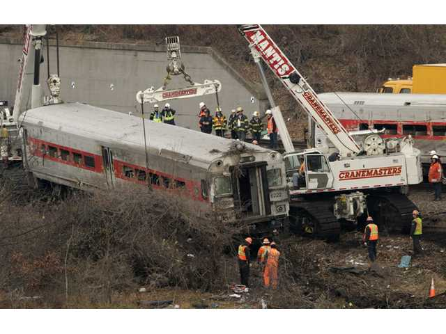 Cranes salvage the last car from from a train derailment in the Bronx section of New York on Monday.