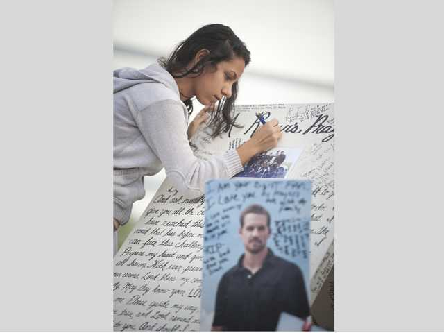 Amanda Guirguis writes a memorial for actor Paul Walker on Monday at a memorial on the site where he was killed in a crash on Saturday. Signal photo by Charlie Kaijo