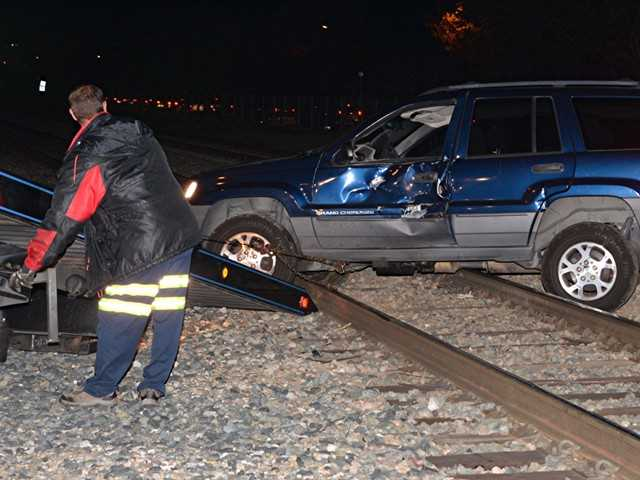 One adult and one child escaped injury when the SUV they were in stalled on the railroad tracks at Newhall Avenue and Railroad Avenue Monday night and was struck by an outbound MetroLink train.  The auto sustained moderate damage and had to be towed off the tracks.  Photo by Rick McClure/For The Signal.