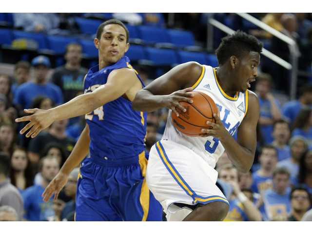 UCLA's Jordan Adams, left, steals the ball on a pass intended for UC Santa Barbara's Michael Bryson on Tuesday in Los Angeles.