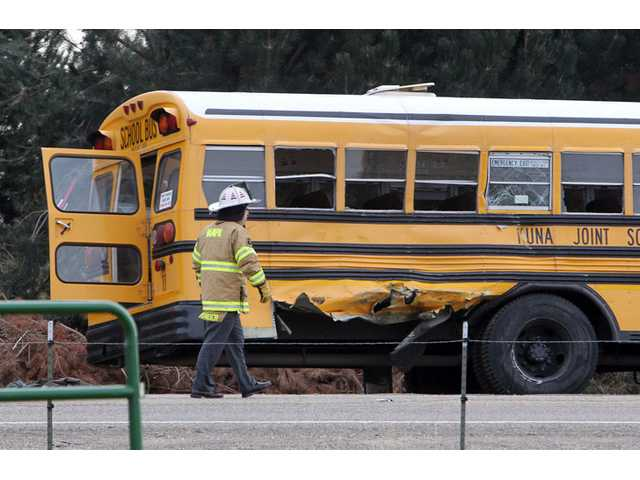 A firefighter walks past the damaged Kuna School District bus at the scene of a fatal crash on Thursday in Kuna, Idaho.