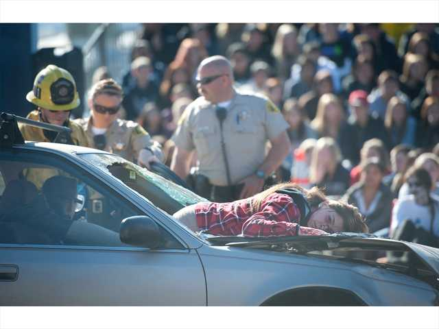 A Saugus High School student depicts a body flung through a windshield to illustrate the dangers of drunk driving at the event. Photo by Charlie Kaijo.