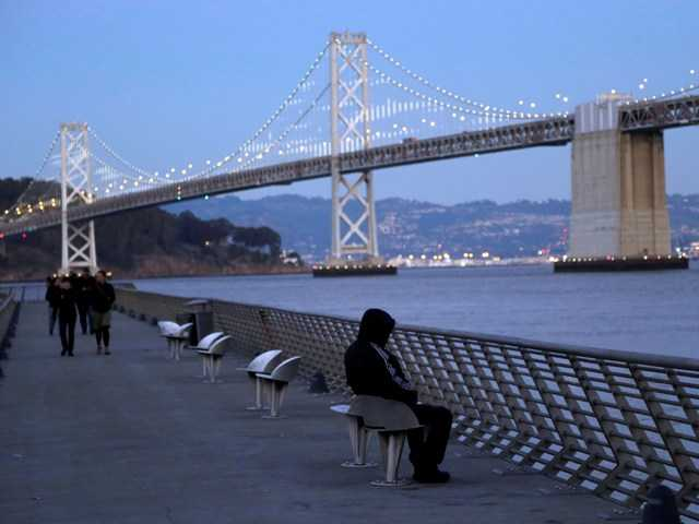 A man sits bundled up by the San Francisco Oakland Bay Bridge. Four homeless people have died of hypothermia in the San Francisco Bay Area since last week.