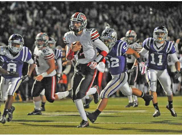 Hart quarterback Brady White (2) runs away from Valencia defenders on Friday night at Valencia High School.
