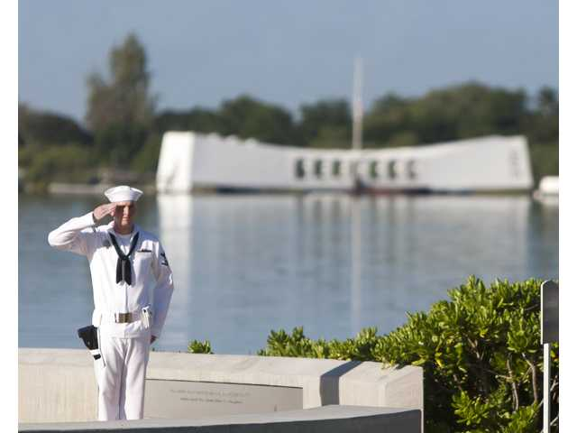 With the USS Arizona in the background, Navy rifleman stands at attention at the ceremony commemorating the 72nd anniversary of the attack on Pearl Harbor on Saturday in Honolulu.