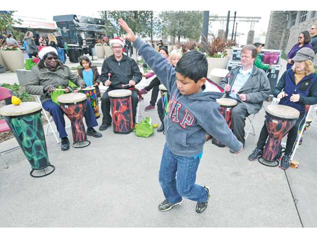 Yash Mehta, 8, dances as a group from the Santa Clarita Valley Senior Center beats a rhythm at the Remo Drum Circle at Santa Clarita's Literacy and Arts Festival held at the Newhall Library on Saturday.