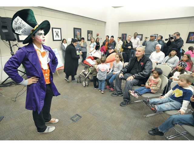 College of the Canyons Teach Program volunteer Jadin Rosas, left, dressed as the The Mad Hatter from Alice in Wonderland, was on hand at the Santa Clarita Literacy and Arts Festival held at the Newhall Library on Saturday.