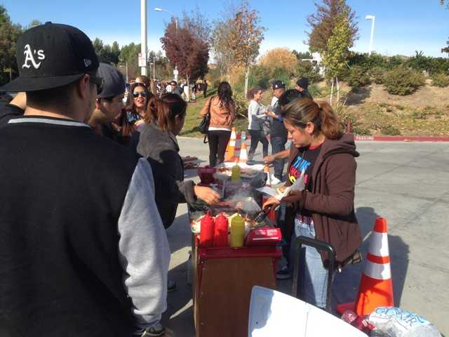 "A hot dog vendor sells her product near the site of the Paul Walker-Roger Rodas memorial Sunday during the social media-planned memorial to the star of the ""Fast & Furious"" series of films."