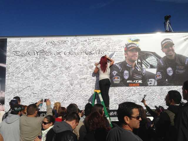 Fans were invited to sign the side of a truck parked in the NorthPark Community Church parking lot Sunday to commemorate Paul Walker and Roger Rodas, who died near the site.