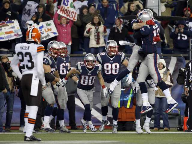 New England Patriots quarterback Tom Brady (12) celebrates his go-ahead touchdown pass with teammates on Sunday.