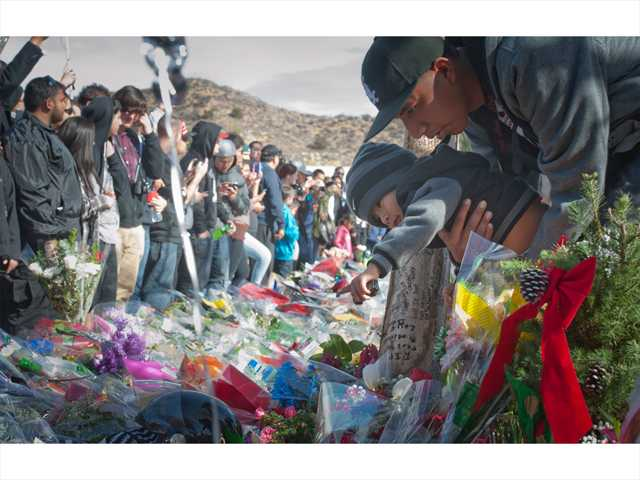 A boy leans in to get a closer look at the Paul Walker memorial as a large crowd gathers around to snap pictures and leave dedications for the actor and his friend Roger Rodas. Signal photo by Charlie Kaijo.