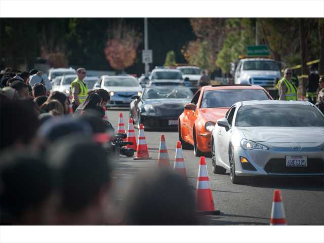 "A line of cars — many of them customized similar to vehicles from the ""Fast & Furious"" film franchise — make their way up Kelly Johnson Parkway to Hercules Street to pass the memorial site where Paul Walker and Valencia business owner Roger Rodas died in a fiery crash last Saturday. Signal photo by Charlie Kaijo."