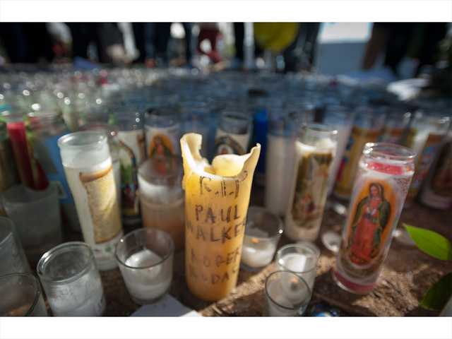 Candles and dedications are left to memorialize the actor Paul Walker and his friend Roger Rodas following their fatal car accident last Saturday. Signal photo by Charlie Kaijo.