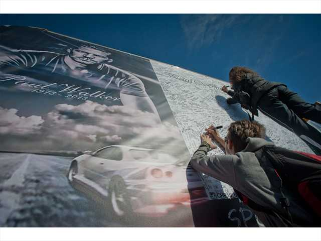 Visitors write messages on a large poster attached to a truck for Walker and his friend Rodas, who investigators say was driving at the time of the fatal crash. Signal photo by Charlie Kaijo.