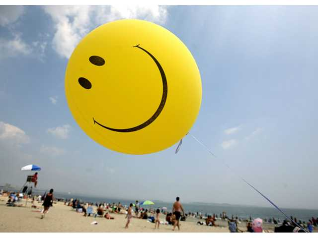 A smiley face balloon floats over Revere Beach in Revere, Mass. as beachgoers head for the water.