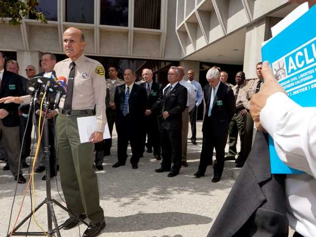 In this Sept. 28, 2011 file photo, Los Angeles County Sheriff Lee Baca, at podium, takes questions about a report released by the American Civil Liberties Union outside Sheriff's headquarters in Los Angeles. Baca has acknowledged mistakes to a county commission reviewing reports of brutality, but he has also defended his department and distanced himself personally from the allegations.