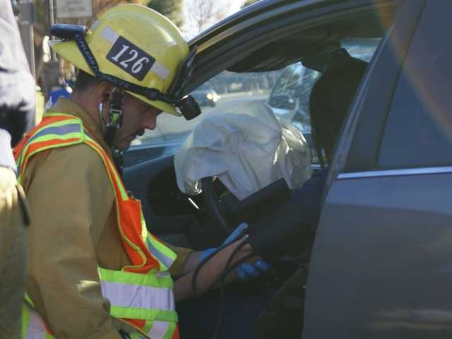 A paramedic with the Los Angeles County Fire Department treats a woman inside a car Monday morning. The car was one of four involved in a traffic collision at the intersection of McBean Parkway and Creekside Road. Signal photo by Jim Holt
