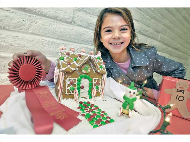 """Sofie Rooney, 8, displays the kids' category second place ribbon she won for her gingerbread house entitled """"Snow-fie's Wonderland"""" at Saturday's contest. Signal photo by Dan Watson."""