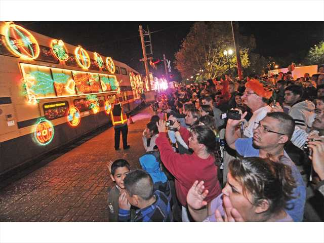 In this November 2012 file photo, a crowd of hundreds watches as the Holiday Toy Express pulls into the Jan Heidt Metrolink station in Newhall. Signal photo by Dan Watson.