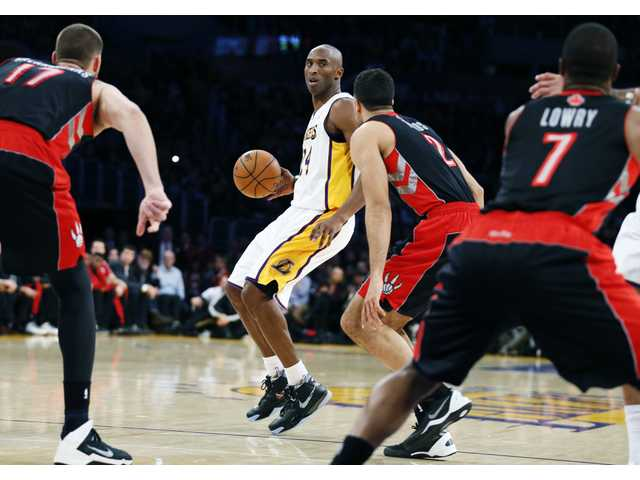 Lakers' guard Kobe Bryant dribbles against the Toronto defense on Sunday at the Staples Center in Los Angeles.
