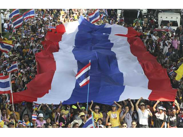Anti-government protesters carry a huge Thai national flag as they march in Bangkok, Thailand on Monday.
