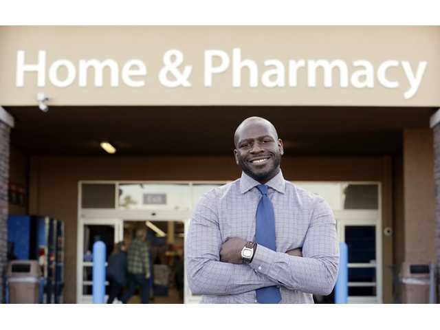 This photo taken Nov. 21, 2013 shows James Lott outside the Wal-Mart store where he works as a pharmacist in Bonney Lake, Wash. Lott, who lives in Renton, Wash., a suburb of Seattle, adds significantly to his six-figure job salary by day-trading stocks.