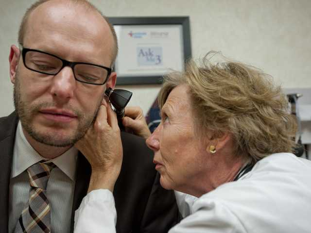 Betsy Bartlett, a family nurse practitioner, examines Michael Vaccaro's ear during a check-up at the Minute Clinic at the CVS store on McBean Parkway in Valencia on Wednesday. Signal photo by Charlie Kaijo.
