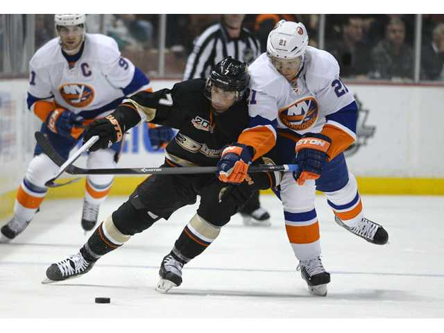 Anaheim Ducks center Andrew Cogliano, left, and New York Islanders right wing Kyle Okposo battle for the puck on Monday in Anaheim.