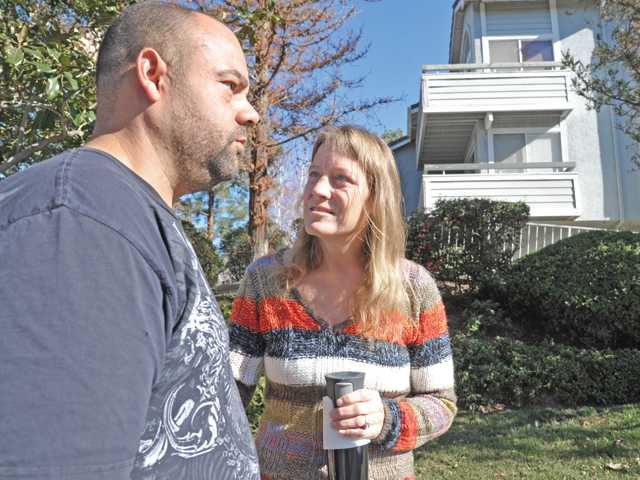 Neighbors Jay Johnson, left and Kristen Booker discuss hearing two loud booms at about 10 p.m. on Tuesday as they stand in front of  the shooting scene on the 26800 block of Claudette Street  in Canyon Country on Wednesday morning. Signal photo by Dan Waston.