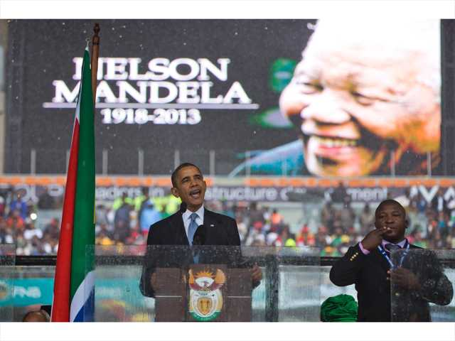 President Barack Obama delivers his speech next to a sign language interpreter during a memorial service at FNB Stadium in honor of Nelson Mandela on Tuesday in Soweto, near Johannesburg.