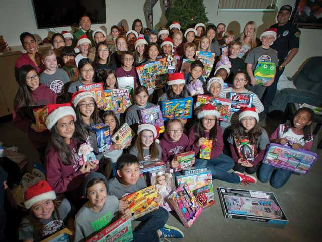 "Fourth, fifth and sixth graders from West Creek Academy pose for a picture with toys they donated to Fire Station Number 156 in Valencia for the 21st annual ""Spark of Love"" Toy Drive on Thursday. Signal photo by Charlie Kaijo."