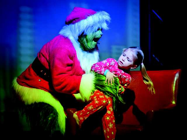 The Grinch snatches away a little girl during Thursday evening's Christmas show at the Real Life Church. Signal photo by Charlie Kaijo.