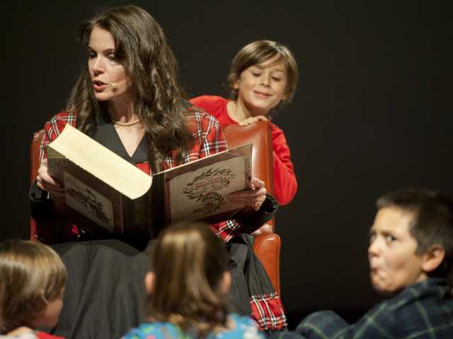 Chana Keefer tells the story of Christmas to children on a stage at Real Life Church Signal photo by Charlie Kaijo.