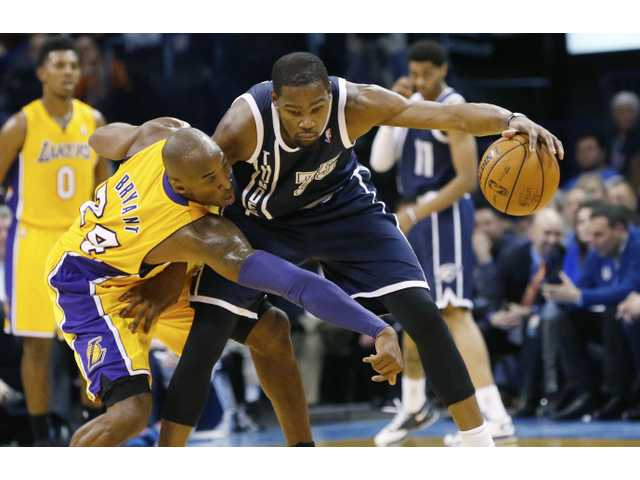 Oklahoma City's Kevin Durant (right) protects the ball from Lakers' guard Kobe Bryant (left) on Friday in Oklahoma City.