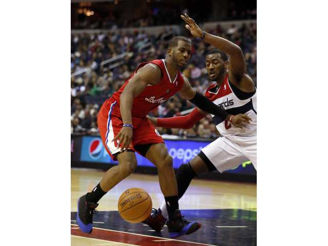 Los Angeles Clippers point guard Chris Paul (3) drives against Washington Wizards point guard John Wall (2) on Saturday in Washington.