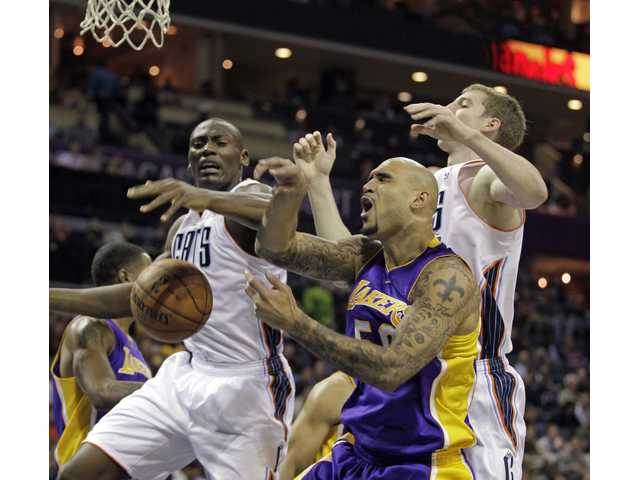 Los Angeles Lakers' Robert Sacre, center, attacks the basket against Charlotte defenders on Saturday.